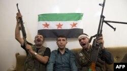 ບຸກຄົນທີ່ສົງໄສວ່າ ເປັນຕຳຫຼວດຂອງລັດຖະບານຊີເຣຍ (ກາງ) ນັ່ງຢູ່ທາງກາງ ສະມາຊິກຂອງພວກກະບົດ Liwa al-Tawhid ຫຼັງຈາກຖືກຈັບ ທີ່ເມືອງ Aleppo (20 ກັນຍາ 2012)
