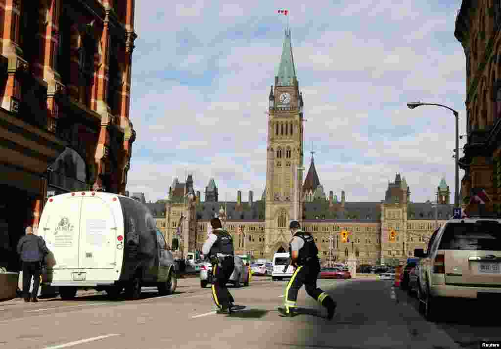 Armed RCMP officers race across a street on Parliament Hilll following a shooting incident in Ottawa, Canada, Oct. 22, 2014.