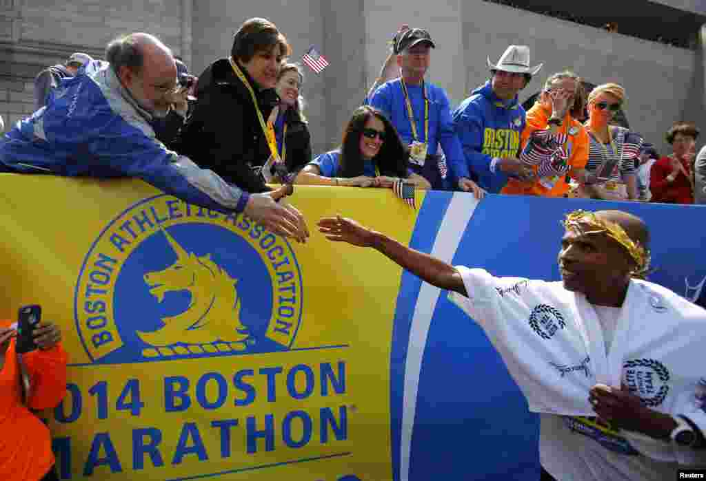 Meb Keflezighi of the U.S. (right) is congratulated after winning the men's division of the 118th running of the Boston Marathon. Keflezighi is the first U.S. male athlete to win the Boston Marathon in three decades, Boston, Mass., April 21, 2014.
