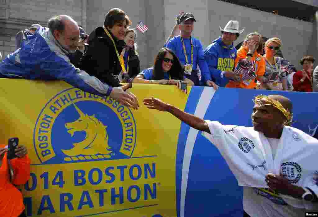 Meb Keflezighi dari AS (kanan) mendapatkan ucapan selamat setelah memenangkan kategori putra dalam Boston Marathon ke-118. Keflezighi adalah atlet pria pertama AS yang memenangkan Boston Marathon selama tiga dekade, Boston, Mass., 21 April 2014.