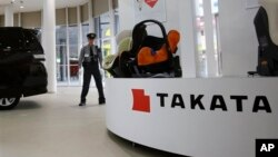 FILE - In this Nov. 6, 2014 file photo, a security guard stands by child seats, manufactured and displayed by Takata Corp. at an automaker's showroom in Tokyo. Japanese automaker Honda Motor Co. expanded its recalls related to defective air bags on Thursd
