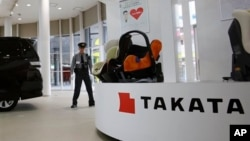FILE - a security guard stands by child seats, manufactured and displayed by Takata Corp. at an automaker's showroom in Tokyo. Japanese automaker Honda Motor Co. expanded its recalls related to defective air bags.
