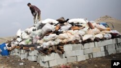 FILE - An Afghan man prepares to set narcotics on fire on the outskirts of Kabul, Oct. 29, 2014.