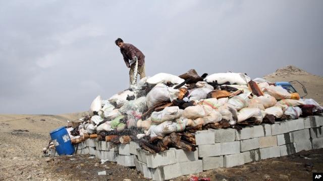 FILE - Афганец готовится установить наркотические средства на огонь на окраине Кабула, 29 октября 2014 года.