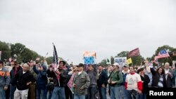 "Protesters with the ""Million Vet March on the Memorials"" rally in front of the National U.S. World War II Memorial in Washington October 13, 2013."