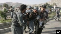 图为阿富汗保安人员8月19日扶着一名在现场受伤的警察
