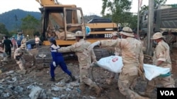 柬埔寨救援人員星期天將一具遺體從倒塌樓房斷壁殘垣中移出。 (美國之音高棉語組)