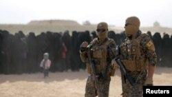 이슬람 극단주의 무장세력 IS의 마지막 장악 지역인 시리아 데이르에조르주의 바구스에서 시리아민주군(SDF)이 탈출하는 주민들 옆으로 걷고 있다.