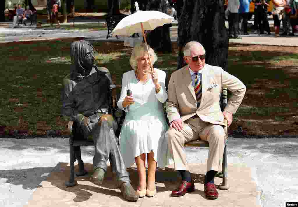 Britain's Prince Charles and Camilla, Duchess of Cornwall, sit on a bench at John Lennon Park in Havana, Cuba.