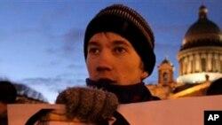 一名俄羅斯反對派活動人士星期一在聖彼得堡的示威中手拿一幅反對普京的海報