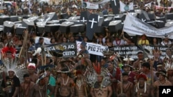 FILE - Indigenous protesters from various ethnic groups carry fake coffins representing indians killed over the demarcation of land, as they demand the demarcation of indigenous lands, outside the National Congress in Brasilia, Brazil, April 25, 2017.