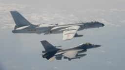 Sebuah jet tempur F-16 Taiwan terbang di sebelah pesawat pengebom H-6 China, atas, di wilayah udara Taiwan, dalam foto yang diambil dan dirilis pada 10 Februari 2020. (Foto: AFP)