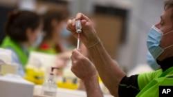 Seorang petugas menyiapkan vaksin COVID-19 produksi AstraZeneca di sebuah klinik kota Antwerpen, di tengah lonjakan kasus COVID-19 di Belgia.