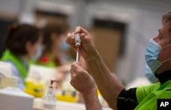 Zdravstveni radnik puni spricu iz bočice vakcine AstraZeneca u Belgiji.