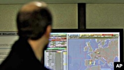 A man walks by a display screen which shows the Libyan 'No-Fly' zone, highlighted in blue at bottom right, at Eurocontrol in Brussels, March 18, 2011