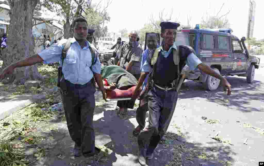 Agentes da polícia transportam um corpo após um carro-bomba ter explodido junto a um café em Mogadíscio, Somália, Fev. 27, 2014.
