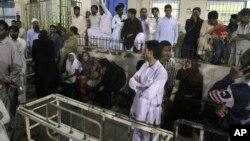 Para anggota keluarga menunggu di rumah sakit yang merawat korban luka-luka serangan bunuh diri di Karachi, Pakistan, Sabtu (12/11).