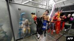 Aktor-aktor 'cosplay' berfoto dalam toilet kaca umum untuk menandai Hari Toilet Dunia di Changsha, provinsi Hunan (19/11).