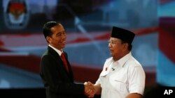 "Indonesia's presidential candidate Joko ""Jokowi"" Widodo (L) shakes hands with his opponent Prabowo Subianto after a debate in Jakarta June 15, 2014."