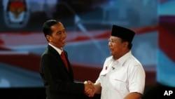 Calon presiden Indonesia Jokowi berjabat tangan dengan Prabowo Subianto sesudah acara debat presiden (15/6). Dalam masa kampanye presiden ini banyak terjadi kampanye hitam seperti misalnya penyebaran tabloid Obor Rakyat yang berisi fitnah terhadap Jokowi.