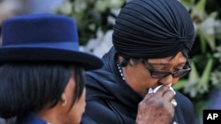 FILE - Winnie Madikizela-Mandela, Nelson Mandela's former wife, walks away after paying her respect to former South African President Nelson Mandela during the lying in state at the Union Buildings in Pretoria, South Africa, Dec. 11, 2013.