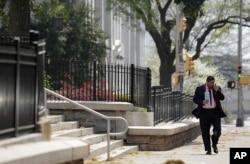 FILE - A pedestrian walks down a street as pollen litters the sidewalk outside the State Capitol Tuesday, March 20, 2012, in Atlanta. (AP Photo/David Goldman)
