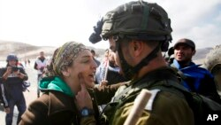 FILE - An Israeli soldier argues with a Palestinian protester as they try to block a highway between Jerusalem and the Dead Sea near the West Bank town of Jericho.