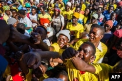 Supporters of ZANU PF cheer for their candidates for parliament after a ZANU PF election campaign rally addressed by Vice President Constantino Chiwenga at a school near Harare, on July 27, 2018.