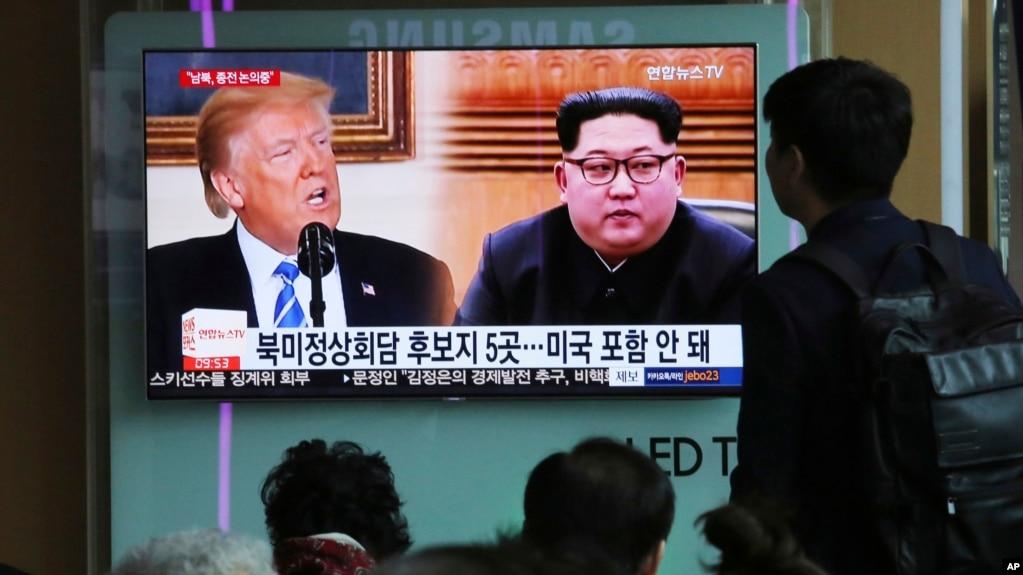 2018年4月18日,在韓國首爾火車站,人們觀看電視新聞節目,屏幕上顯示美國總統唐納德·川普和朝鮮領導人金正恩各自的肖像。