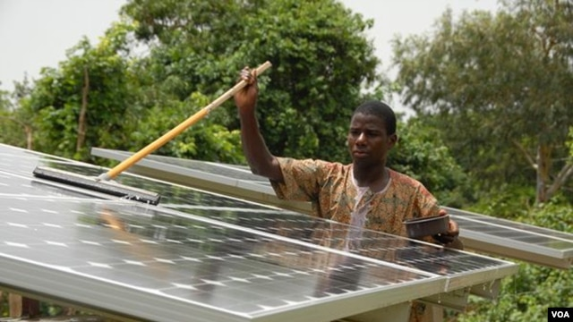 A Beninese man cleans one of the solar panels that has electrified his village (Courtesy SELF)