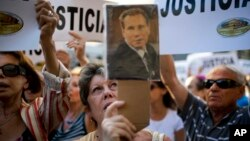 FILE - A woman sings the Argentine national anthem while holding a portrait of the late prosecutor Alberto Nisman outside the AMIA Jewish community center in Buenos Aires, Argentina, Jan. 21, 2015.