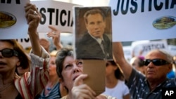 FILE - A woman holds a portrait of the late prosecutor Alberto Nisman outside the AMIA Jewish community center in Buenos Aires, Argentina, Jan. 21, 2015.