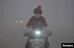 Phụ nữ đạp xe trên đường phố bao trùm trong khói mù ở tỉnh Sơn Đông, Trung Quốc.