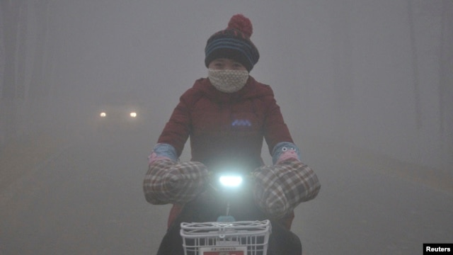 FILE - With a yellow smog alert in effect, a woman rides her electric bicycle along a street amid thick haze in Chiping county, Shandong province, China, Jan. 16, 2015.
