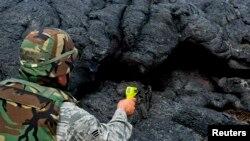 Un guardia nacional toma la temperatura de la lava en Puna, cerca del pueblo de Pahoa, Hawái.