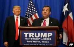 ຜູ້ສະໝັກ ປະທານາທິບໍດີ ພັກຣີພັບບລິກັນ ທ່ານ Donald Trump ຍີ້ມຫົວ ໃນຂະນະທີ່ ຜູ້ປົກຄອງລັດ New Jersey ທ່ານ Chris Christie ກ່າວຄຳປາໄສ ທີ່ເມືອງ Ft Worth ລັດ Texas.
