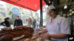 Menepuk-nepuk, membentuk, dan memanggang adonan roti untuk membuat roti khas bagi pasar-pasar swalayan kelas atas dan restoran-restoran bergengsi di New York adalah salah satu pelajaran di toko roti Hot Bread Kitchen yang diberikan kepada perempuan-perempuan imigran yang ingin berkarir menjadi pembuat roti (foto: Dok).