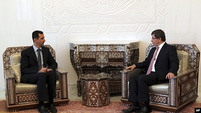 Turkish Foreign Minister Ahmet Davutoglu, right,  meets with Syrian President Bashar al-Assad. in Damascus,  August 9, 2011