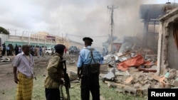 Soldiers look from a distance at the scene of a suicide attack in Mogadishu July 12, 2013.