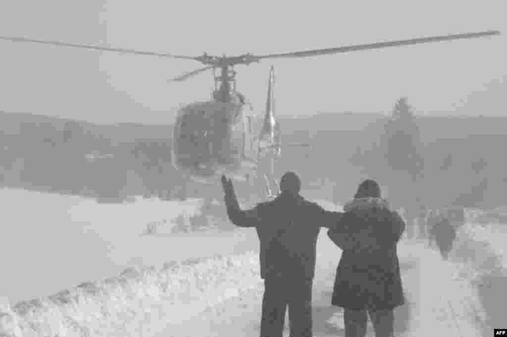 Dân làng Bosnia cách thủ đô Sarajevo 70 kilomet ra hiệu cho máy bay trực thăng đến tiếp tế, vì làng của họ không thể đến bằng ôtô, 1 tháng 2, 2012. (AP)