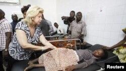L'épouse du président Alassane Ouattara, Dominique, au chevet des personnes blessées lors de la bousculade qui s'est produite après des feux d'artifice à Abidjan, 1er Janvier 2013. Plus de 60 personnes ont été écrasées à mort dans une bousculade devant un stade.