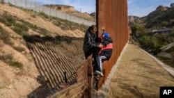 Tư liệu - Một di dân người Honduras giúp con trai của ông ta trèo qua hàng rào biên giới của Mỹ trước khi nhảy vào lãnh thổ của Mỹ ở San Diego, bang California từ Tijuana, Mexico, ngày 22 tháng 12, 2018.