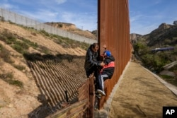 FILE - A Honduran migrant helps his son to climb the U.S. border fence before jumping into the United States to San Diego, Calif., from Tijuana, Mexico, Dec. 22, 2018.