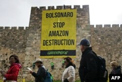 Para wisatawan berjalan melewati para aktivis Greenpeace yang sedang menggantungkan spanduk besar pada pembatas Kota Tua Yerusalem dengan pesan mengenai hutan Amazon untuk Presiden Brasil yang sedang berkunjung ke Yerusalem, 1 April 2019. (Foto: AFP)