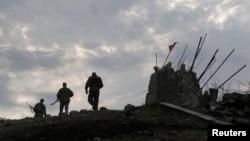 ພວກກະບົດແບ່ງແຍກດິນແດນນິຍົມຣັດເຊຍ ຍ່າງຜ່ານ ອະນຸສາວະລີສົງຄາມ Savur-Mohyla ທີ່ຖືກທຳລາຍ ເທິງພູແຫ່ງນຶ່ງ ທາງກ້ຳຕາເວັນອອກຂອງເມືອງ Donetsk 28 ສິງຫາ 2014)