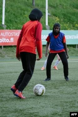 Kamila Nuh (kiri) dan Nasro Bahnaan Hulbade, keduanya mengenakan jilbab olahraga, berlatih sepak bola di Stadion MUP di Vantaa, Finlandia, 1 Juni 2021. (AFP)