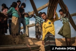 Rohingya refugees carry bamboo poles distributed by aid groups to reinforce shelters in the Kutupalong refugee camp. The aid groups are also handing out plastic sheeting.