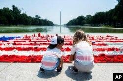 미국 독립기념일을 하루 앞둔 7월 3일, 워싱턴 d.c.의 링컨 기념관 앞에서 어린아이들이 레고로 만든 성조기를 보고 있다.