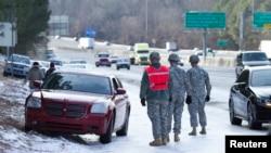 Miembros de la Guardia Nacional ayudan a sacar un auto varado en una carretera de Atlanta.