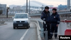FILE - Russian traffic police stand guard on a road near venues at the Olympic Park near Sochi, Jan. 7, 2014.